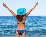 Woman enjoying warm summer day at a seaside. Stock Photos