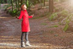 Woman enjoying the warmth of winter sunlight alone on forest park path with arms open. Receiving rays of light, wearing a red long coat or overcoat stock images