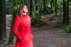 Woman enjoying the warmth of the winter sunlight on a forest. Wearing a red overcoat stock photo