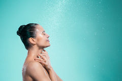 Woman enjoying water in the shower under a jet Stock Photo