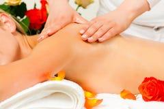 Woman enjoying wellness back massage Stock Photos