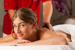 Woman enjoying wellness back massage Stock Images