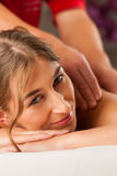 Woman enjoying wellness back massage Stock Photos