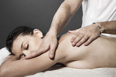 Woman enjoying a wellness back massage in a spa, she is very rel Stock Photo