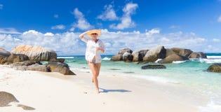 Woman enjoying white sandy beach on Mahe Island, Seychelles. Happy woman wearing white loose tunic over bikini and beach hat, enjoying amazing white sandy beach Royalty Free Stock Images