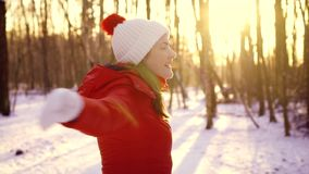 Woman enjoying winter day outdoors. Happy girl raising arms up in slow motion and whirling around stock video