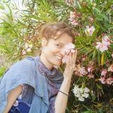 Woman enjoyng Oleander plant Royalty Free Stock Photography