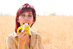 Woman enjoys a banana. Woman eats a banana fruit with calcium and potassium outdoors Stock Photography