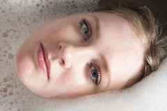 Woman enjoys the bath-foam in the bathtub. Royalty Free Stock Photos