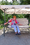 Woman enjoys the bench at the park Stock Image