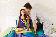 Woman enjoys breakfast in bed. Pregnant women enjoys breakfast in bed brought by husband Stock Photos