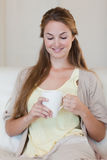 Woman enjoys having a coffee on her couch Royalty Free Stock Photo
