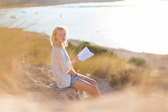 Woman enjoys reading on beautiful sandy beach. Royalty Free Stock Photo