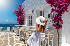 Woman enjoys the setting on the Cyclades islands of Greece. Beautiful tourist woman enjoys the setting of white houses on the Cyclades islands of Greece during stock photo