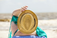 Woman enjoys sitting at the beach Royalty Free Stock Photo