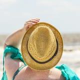 Woman enjoys sitting at the beach Stock Photos