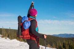 Woman enjoys the success of climbing in the mountains in winter. Royalty Free Stock Photography