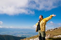 Woman enjoys sun in mountains on hiking Stock Photography