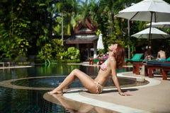 Woman enjoys a sunny day relaxing. Beautiful woman sitting in bikini near swimming pool Stock Photography