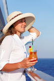 Woman enjoys traveling sipping a cocktail Stock Photography