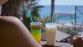 Woman enjoys the view of sea on a terrace with two cocktails. Close up shor of two cocktails standing on a sunny terrace. Woman takes one to drink while she stock video