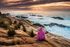 Woman enjoys views of sunbeams and sea flows. Female in pink hoodie relaxes on coastal rocks watching the sunbeams and sea flows over the craggy rocky coast royalty free stock images