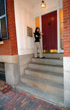 Woman entering city apartment. A young woman unlocking the entrance to her city apartment stock images