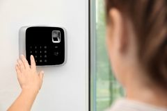 Woman entering code on alarm system keypad indoors stock images