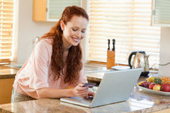 Woman entering credit card information Stock Photography