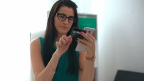 Woman entering data using smartphone while holding a credit card in the other hand.  stock video footage