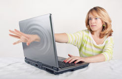 Woman entering digital world. Amazed woman putting hand through screen of open laptop computer and entering digital world, white background with copy space Royalty Free Stock Photo