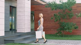 Woman entering luxury apartments with shopping bag. Female customer coming home. Woman entering luxury apartments with shopping bag. Shopping woman going up stock footage