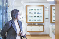 Woman entering into an optician store Stock Images
