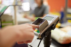 Woman entering pin code at store cash register Stock Images