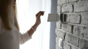 Woman entering pin on home security alarm keypad stock footage