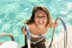 Woman entering pool royalty free stock photo