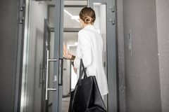 Woman entering residential building. Young business woman in white suit entering to the hall of the modern reential building, back view stock photo
