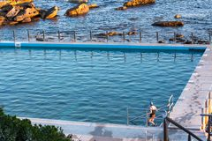 Woman entering seaside ocean swimming pool set against calm blue water and large exposed rocks. Woman entering seaside ocean swimming pool set against calm blue royalty free stock image