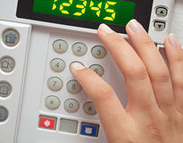 Woman entering security code to alarm system. Closeup photo of a hand of a woman entering security code to alarm system Stock Photos