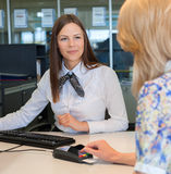 Woman entering security details for credit card. In bank Royalty Free Stock Photography