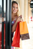 Woman entering a store. A young woman entering a store Stock Images