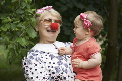Woman is entertaining her little granddaughter. With a clown nose Stock Photo