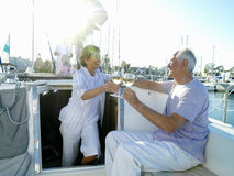 Woman in entrance to cabin of boat with drink, making toast with man (lens flare) Stock Photography