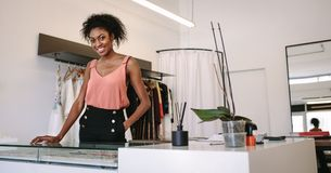 Woman entrepreneur in her boutique. Female fashion designer standing at her desk in her boutique. Female dress designer in her cloth shop with designer clothes Royalty Free Stock Photo