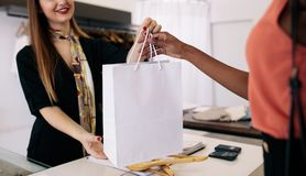 Woman entrepreneur making sale in her fashion studio. Customer shopping designer wear at a fashion boutique. Woman entrepreneur handing over shopping bag to the royalty free stock photo