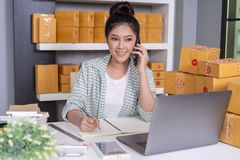 woman entrepreneur talking with customer on mobile phone and writing product order at home office royalty free stock images