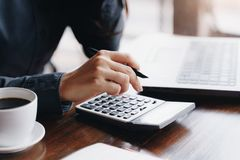 Woman entrepreneur using a calculator to calculating financial expense at coffee shop.  stock image