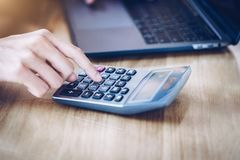 Woman entrepreneur using a calculator to calculating financial expense at home office royalty free stock photography