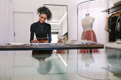 Woman entrepreneur at work in her boutique. Female fashion designer sketching a design sitting at her table. Fashion entrepreneur engrossed in making a drawing Stock Photography