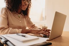 Woman entrepreneur working from home on laptop. Businesswoman working on laptop computer from home. Woman entrepreneur sitting at home working on laptop with royalty free stock image